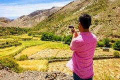 Turista que filma un valle en las montañas de atlas Imagen de archivo