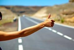 turista que hace autostop a lo largo de un camino Imagen de archivo libre de regalías