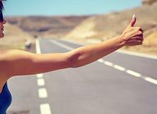 turista que hace autostop a lo largo de un camino Fotos de archivo