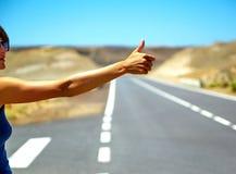 turista que hace autostop a lo largo de un camino Foto de archivo
