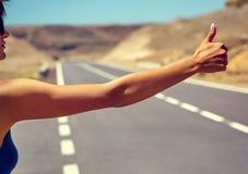 turista que hace autostop a lo largo de un camino Fotografía de archivo libre de regalías