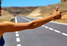 turista que hace autostop a lo largo de un camino Imagen de archivo