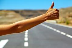 turista que hace autostop a lo largo de un camino Foto de archivo libre de regalías