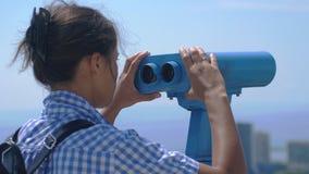 Turista que mira a través de los prismáticos Sochi Mujer joven con la mochila que mira a través de los prismáticos de una torre a Fotografía de archivo libre de regalías