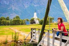 Turista que relaxa na ponte na vila Oppstryn Noruega Imagens de Stock