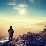 Turista que se coloca en punto de visión rocoso y que mira en el valle brumoso Fotografía de archivo libre de regalías