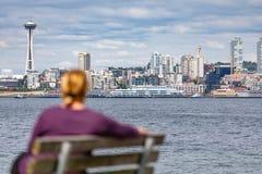 Turista que se sienta en el banco que mira la Seattle, Washington Skyline foto de archivo