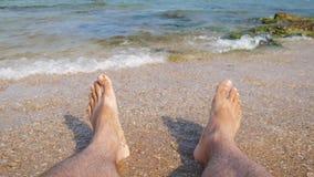 Turista que se sienta en la playa y que consigue sus pies mojados debido a una onda almacen de video