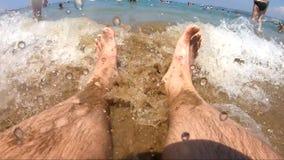 Turista que se sienta en la playa y que consigue sus pies mojados debido a una onda almacen de metraje de vídeo