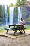 Turista que se sienta en la tabla y que tiene comida Cascada de Kerikeri, Nueva Zelanda Fotos de archivo libres de regalías