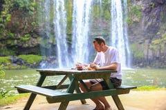 Turista que se sienta en la tabla y que tiene comida Cascada de Whangarei, Nueva Zelanda Foto de archivo libre de regalías