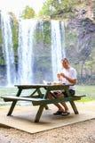 Turista que se sienta en la tabla y que tiene comida Cascada de Whangarei, Nueva Zelanda Imágenes de archivo libres de regalías