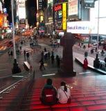Turista que se sienta en pasos de progresión del Times Square Fotos de archivo libres de regalías