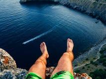 Turista que se sienta encima de la montaña sobre pies que cuelgan del mar al aire libre fotos de archivo