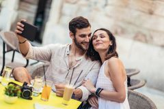 Turista que senta-se em um café, café bebendo e tomando o selfie imagens de stock