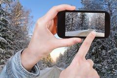Turista que toma a foto da estrada do inverno na floresta da neve Imagens de Stock Royalty Free