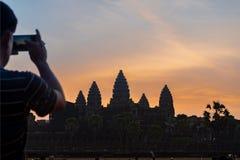 Turista que toma a foto de Angkor Wat no nascer do sol imagens de stock royalty free