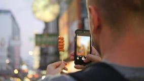 Turista que toma a foto de salsichas deliciosas do alimento da rua na cidade de China Homem novo no festival do vegetariano em Ba video estoque