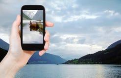 Turista que toma a foto do fiorde em Noruega na noite Imagem de Stock Royalty Free