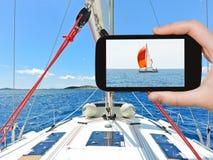 Turista que toma a foto do iate vermelho no mar de adriático Foto de Stock Royalty Free