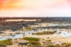 Turista que toma a foto na costa rochoso das Ilhas Canárias Imagem de Stock Royalty Free