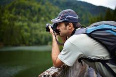 Turista que toma fotos de um lago Imagens de Stock