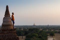 Turista que toma las fotos de la salida del sol en la pagoda superior en Myanmar, Bagan Foto de archivo libre de regalías