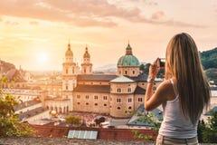 Turista que toma uma foto do por do sol bonito em Salzburg Áustria Imagens de Stock