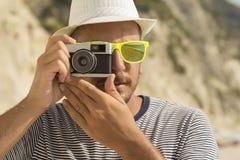 Turista que toma una foto en la playa usando cámara retra Imagen de archivo