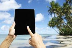 Turista que viaja que usa la tableta en la playa en Nordeste Bahia Brazil Fotografía de archivo libre de regalías