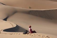 Turista relaxado que senta-se em dunas de areia em um deserto e que olha a vista Imagem de Stock Royalty Free