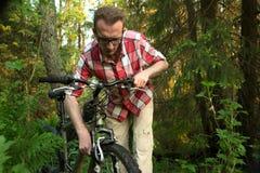 Turista, repearing a bicicleta nas madeiras Imagem de Stock