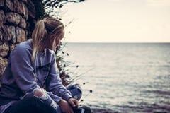 Turista solo pensativo de la mujer joven con los ojos cerrados que piensa durante su viaje que se sienta en la costa en estilo re Foto de archivo