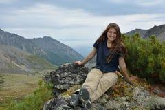 Turista sonriente de la muchacha con un cuchillo de caza que se sienta en el top Imagenes de archivo