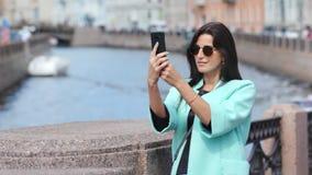 Turista sonriente de la mujer de moda que toma la foto usando la situación del smartphone en el puente sobre el río almacen de metraje de vídeo