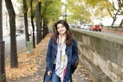 Turista sorridente cinese che cammina sulla via di autunno con le foglie cadute in Europa Fotografie Stock Libere da Diritti
