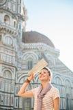 Turista sorridente della donna con la mappa che fa un giro turistico a Firenze, Italia Immagini Stock Libere da Diritti