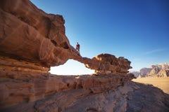 Turista su roccia Deserto di Wadi Ram Lapidi il ponticello Paesaggio della Giordania Immagine Stock Libera da Diritti