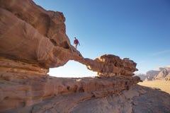 Turista su roccia Deserto di Wadi Ram Lapidi il ponticello Paesaggio della Giordania Immagini Stock Libere da Diritti