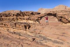 Turista su roccia Deserto di Wadi Ram Lapidi il ponticello Paesaggio della Giordania Fotografia Stock