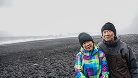 Turista superior dos pares de Islândia na praia preta Fotos de Stock Royalty Free