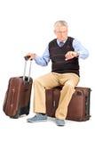 Turista superior que verifica o tempo assentado em sua bagagem Fotos de Stock