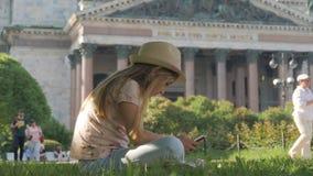 Turista teenager della ragazza che si siede cercando informazioni su uno Smart Phone sulle vacanze sulla via della città Tecnolog archivi video