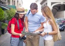 Turista tres que mira el mapa en la calle Fotos de archivo