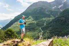 Turista in una maglietta del cappuccio e shorts con un totalizzatore con un telefono nelle mani nelle montagne e nella prova chia Fotografia Stock
