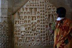 Turista vicino agli scupltures di Tirthankara Tempiale Jain Ranakpur Il Ragiastan L'India Fotografie Stock Libere da Diritti