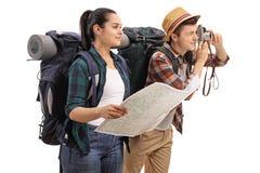 Turistas adolescentes con un mapa y una cámara Fotos de archivo libres de regalías