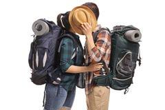 Turistas adolescentes que se besan y que ocultan detrás de un sombrero Imágenes de archivo libres de regalías