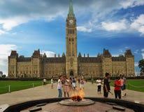 Turistas al lado de la llama centenaria delante del parlamento principal del edificio de Canadá Imagen de archivo