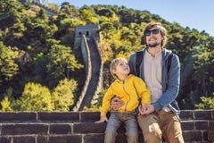 Turistas alegres alegres felizes paizinho e filho no Grande Muralha de China que tem o divertimento no riso do curso e na dança d foto de stock
